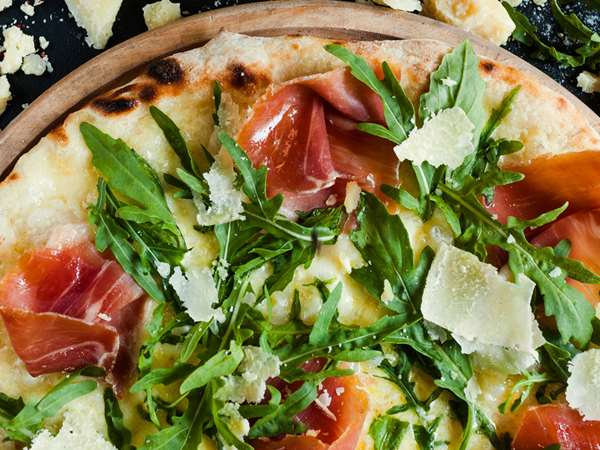 Pizza with procuito, arugula and parmesan